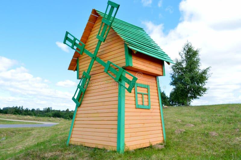 一个美丽的木磨房是一台土气自然风车由黄色和绿色日志做成板反对与云彩的蓝天 库存图片