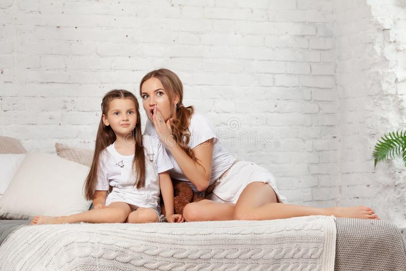 一个美丽的母亲的室内画象有她的摆在反对卧室内部的迷人的矮小的女儿 库存图片