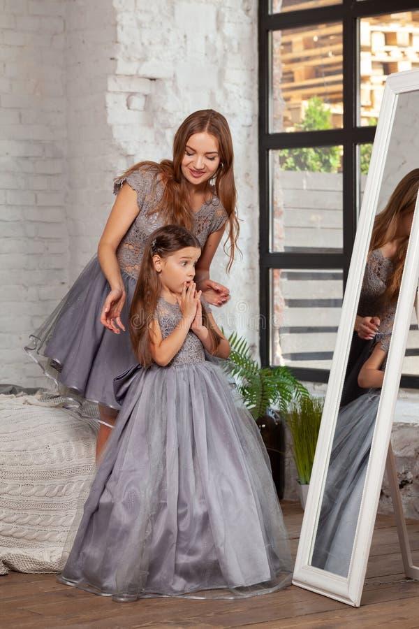 一个美丽的母亲的室内画象有她的摆在反对卧室内部的迷人的矮小的女儿 免版税库存照片