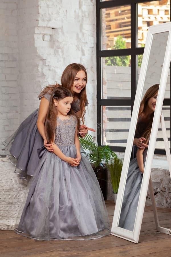 一个美丽的母亲的室内画象有她的摆在反对卧室内部的迷人的矮小的女儿 图库摄影