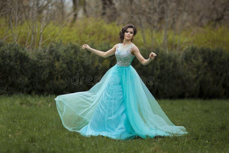 一个美丽的毕业生女孩在一件蓝色礼服转动  一件美丽的礼服的典雅的少妇在公园 免版税库存照片