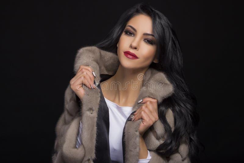 一个美丽的浅黑肤色的男人的画象皮大衣的 图库摄影