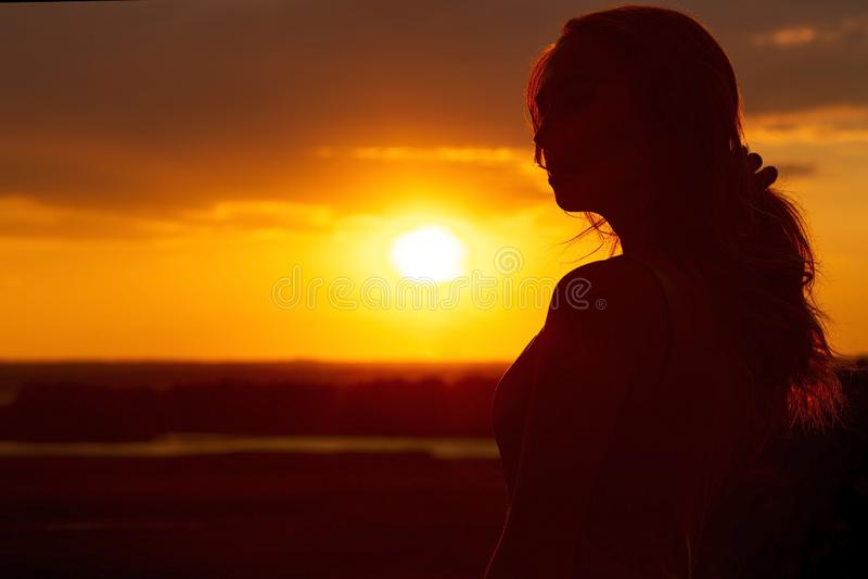 一个美丽的浪漫女孩的剪影日落的,年轻女人的面孔外形有长发的在酷暑 库存图片