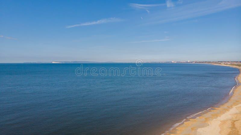 一个美丽的海滩的一张鸟瞰图与水晶大海的在一庄严天空蔚蓝和一些白色云彩下 免版税库存照片