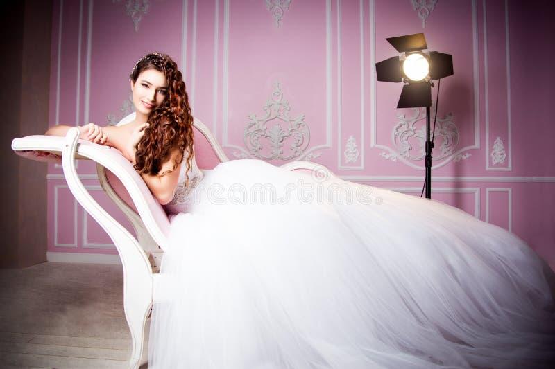 一个美丽的深色的新娘的迷人的照片说谎在桃红色沙发的一套豪华婚礼礼服的 库存照片
