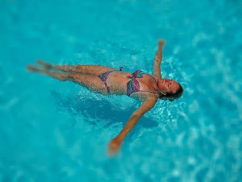 一个美丽的白人妇女的画象在一个水池的透明水的中享受松弛镇静时间游泳在一好日子  免版税库存图片