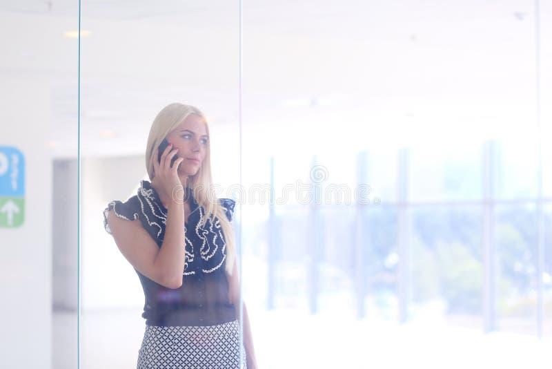 一个美丽的白肤金发的女商人在电话谈话 免版税库存照片