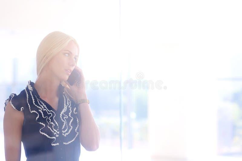 一个美丽的白肤金发的女商人在电话谈话 库存图片