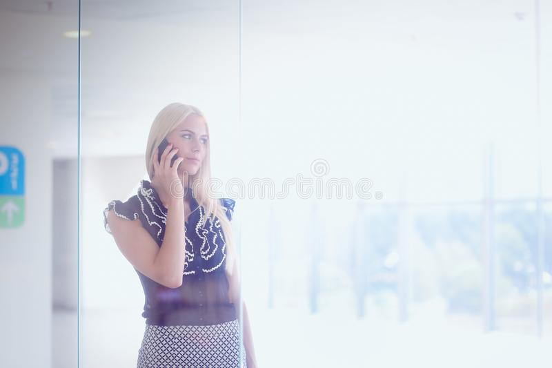 一个美丽的白肤金发的女商人在电话谈话 库存照片