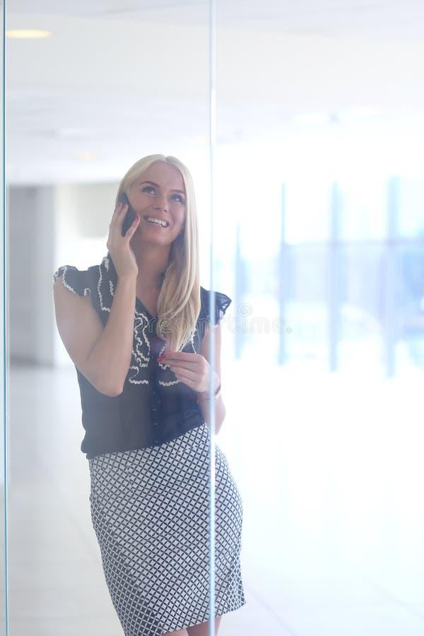 一个美丽的白肤金发的女商人在电话谈话 免版税图库摄影
