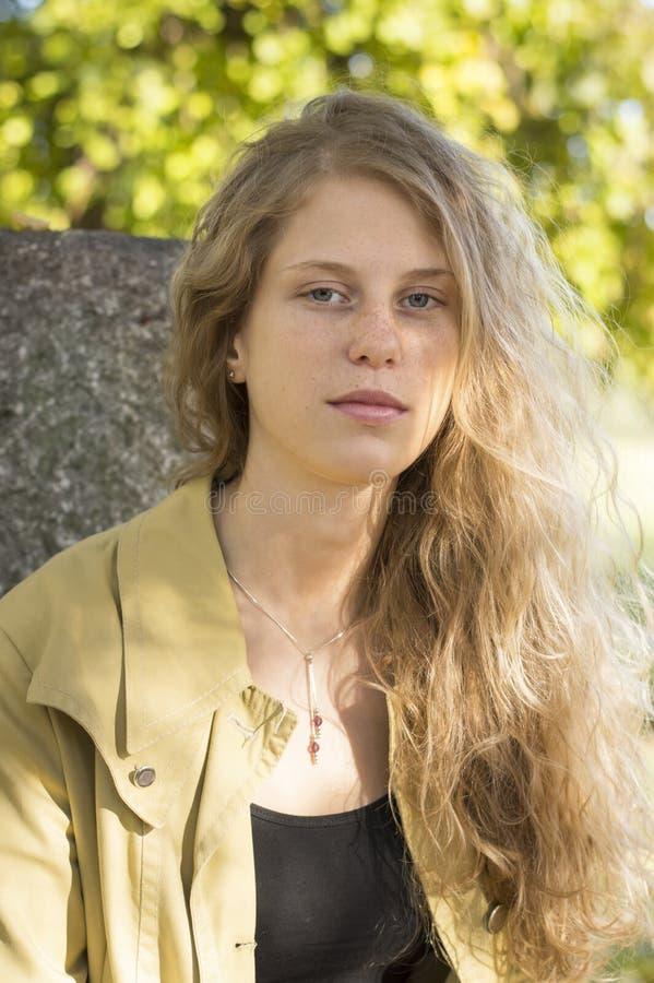 一个美丽的白肤金发的女孩的画象在公园 免版税库存图片