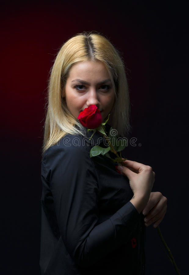 一个美丽的白肤金发的女孩的画象有一朵红色玫瑰的在她的手上 库存图片