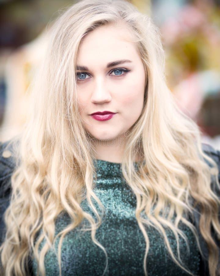 一个美丽的白肤金发的蓝眼睛的十几岁的女孩的画象以绿色 库存图片