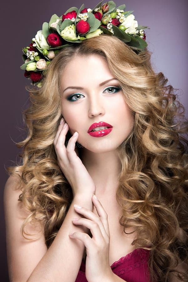 一个美丽的白肤金发的紫色花女孩和花圈的画象有卷毛的在她的头的 秀丽表面 库存照片