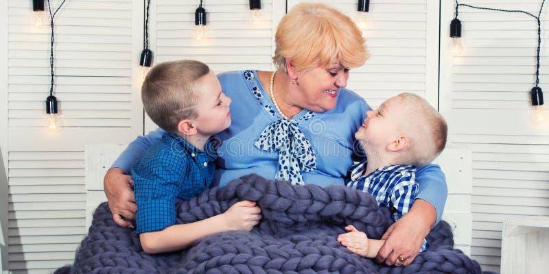 一个美丽的祖母和两个孙子坐沙发在一条被编织的美利奴绵羊的羊毛毯子下 愉快的系列 图库摄影
