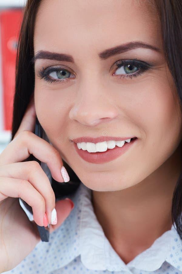 一个美丽的笑的女孩的特写镜头画象谈话在手机 库存照片