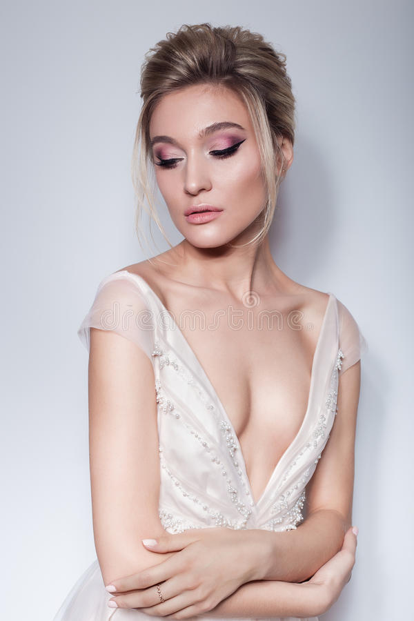 一个美丽的精美女孩的画象空气新娘桃红色礼服的有在桃红色口气和美丽的婚礼hairstyl的明亮的构成的 免版税库存图片