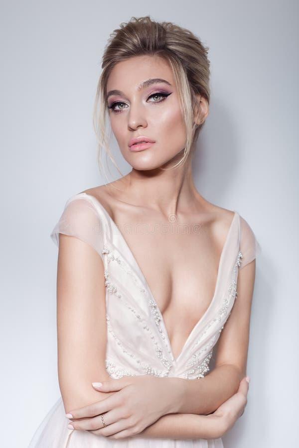 一个美丽的精美女孩的画象空气新娘桃红色礼服的有在桃红色口气和美丽的婚礼hairstyl的明亮的构成的 库存图片