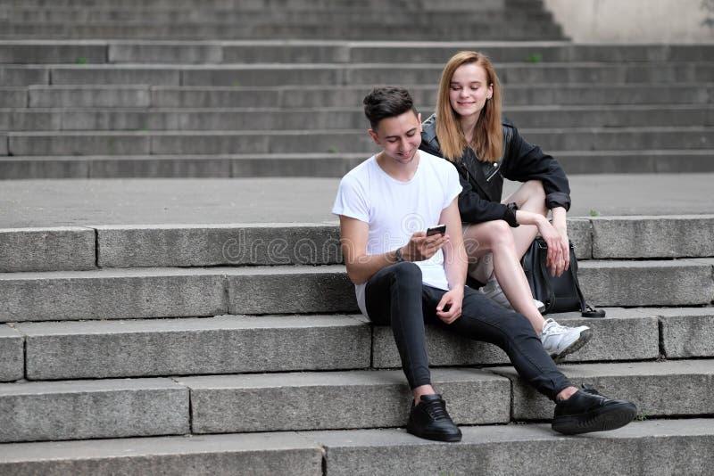 一个美丽的红发女孩和一个深色的人看了事有趣在他们的手机 免版税库存照片