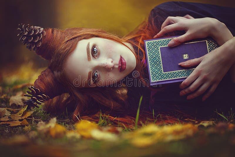 一个美丽的红发女孩的画象有一种异常的发型的与一本书在秋天神仙的森林A美妙的秋天 免版税图库摄影