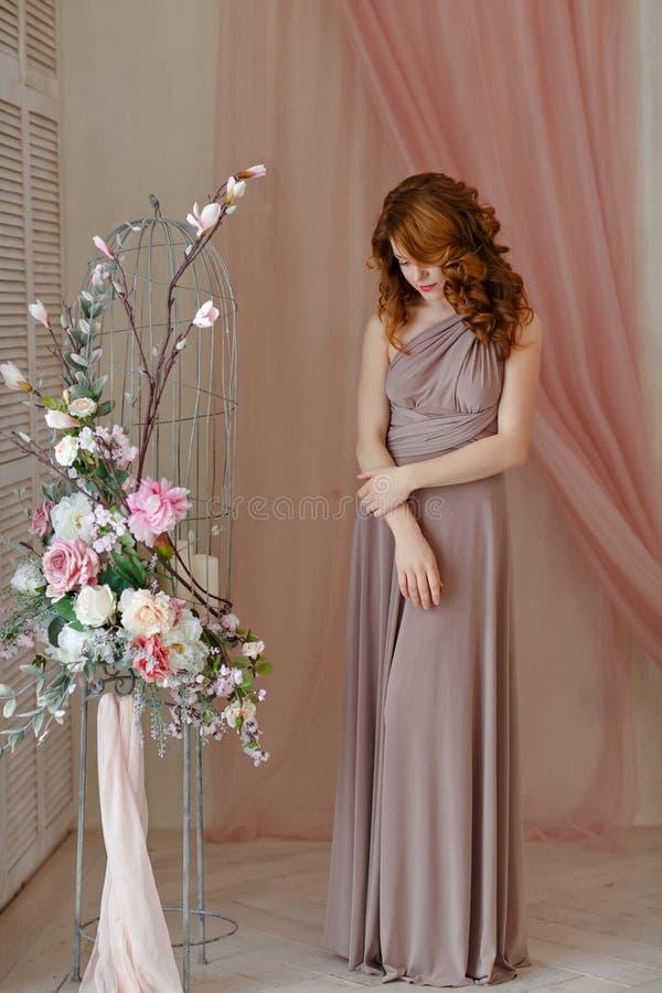 一个美丽的红发女孩的画象一件灰色礼服的在f 免版税库存图片
