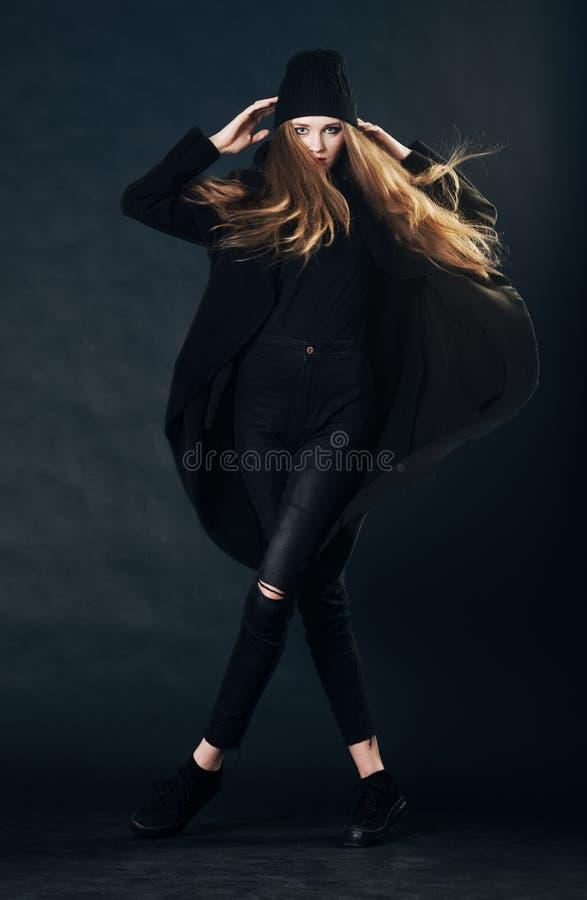 一个美丽的红发女孩的画象黑衣裳的 图库摄影