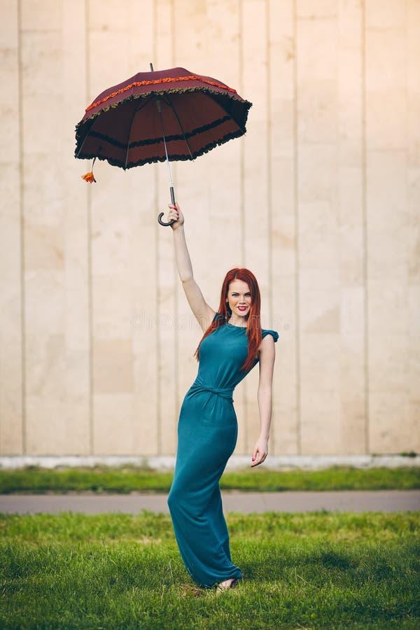 一个美丽的红发少妇的画象有伞的 免版税库存照片
