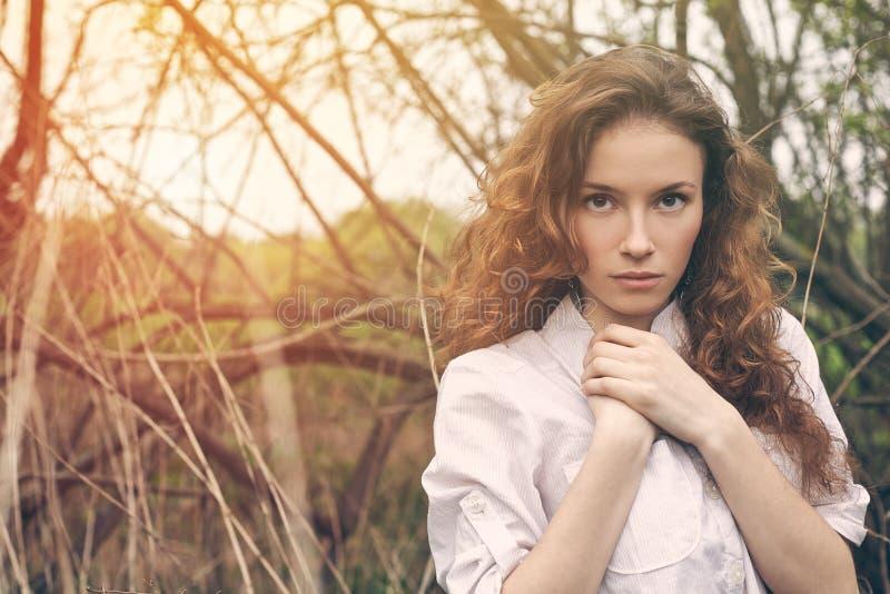 一个美丽的红头发人卷曲女孩的室外画象 免版税库存照片