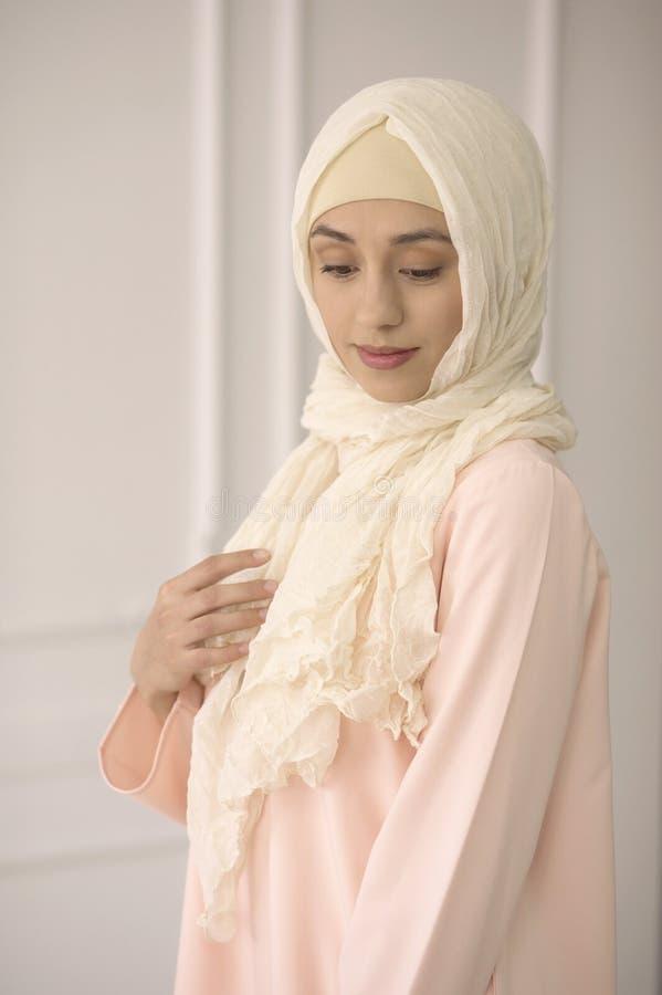 一个美丽的聪慧的穆斯林的东部女孩穿戴,在她的头的一件披肩在轻的古典背景 库存图片