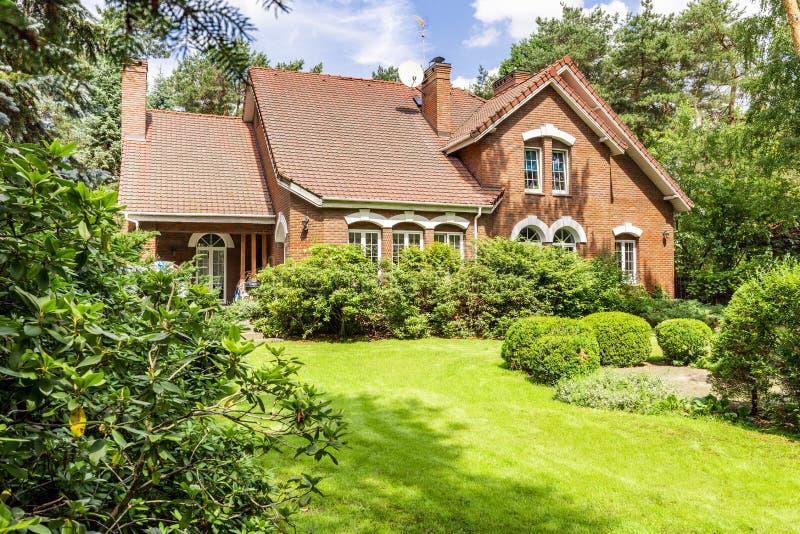 一个美丽的英国样式房子的后院有灌木和gree的 免版税库存照片