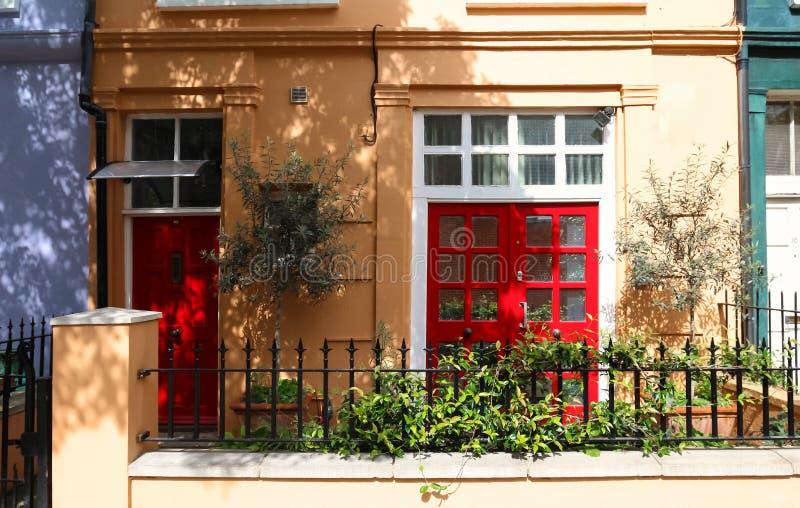 一个美丽的英王乔治一世至三世时期时代城内住宅的前面红色门在伦敦 免版税图库摄影