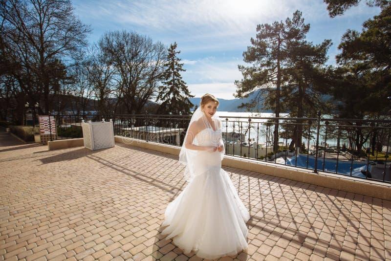 一个美丽的计算的新娘沿码头漫步并且敬佩小山和蓝色晴朗的天空 免版税库存照片