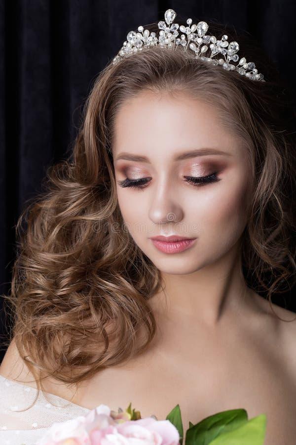 一个美丽的逗人喜爱的愉快的新娘的柔和的画象有美好的发型欢乐明亮的构成的在与的耳环的一套婚礼礼服 图库摄影
