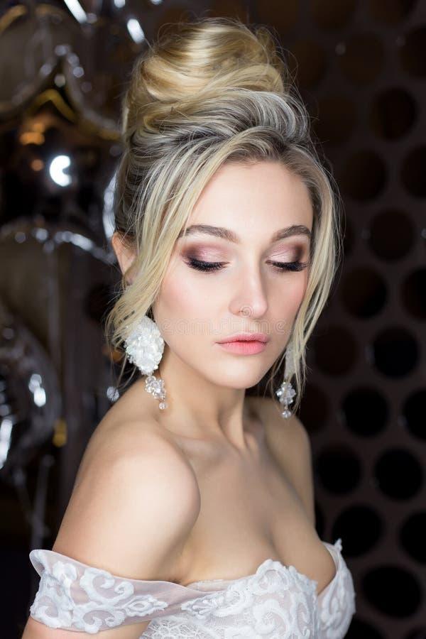 一个美丽的逗人喜爱的愉快的新娘的柔和的画象有美好的发型欢乐明亮的构成的在与的耳环的一套婚礼礼服 库存图片