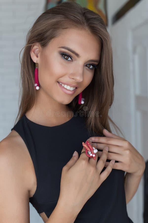 一个美丽的逗人喜爱的柔和的美丽的女孩的画象有雪白微笑的与在黑晚礼服的明亮的构成有珠宝的 库存图片