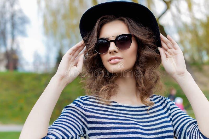 一个美丽的逗人喜爱的年轻微笑的女孩的画象黑帽会议和太阳镜的在都市样式 库存图片