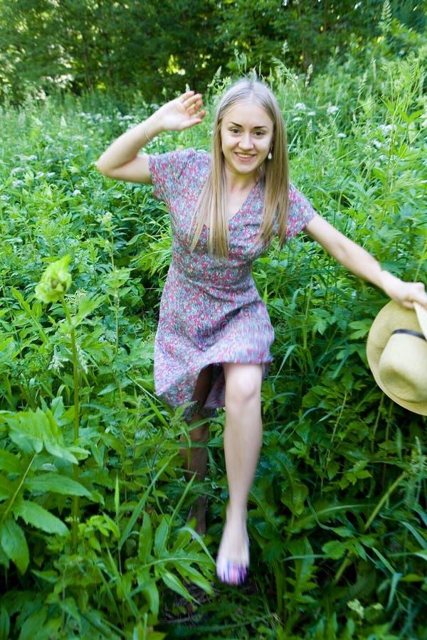 一个美丽的金发碧眼的女人通过高草丛林做她的方式 免版税库存照片