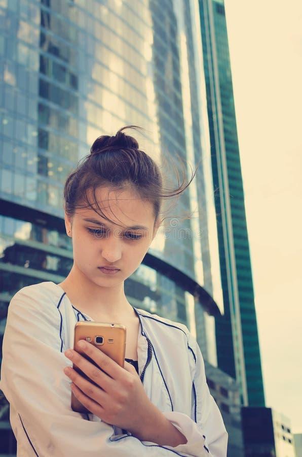 一个美丽的青少年的女孩在现代大厦背景在她的手上站立并且拿着一个智能手机 免版税图库摄影