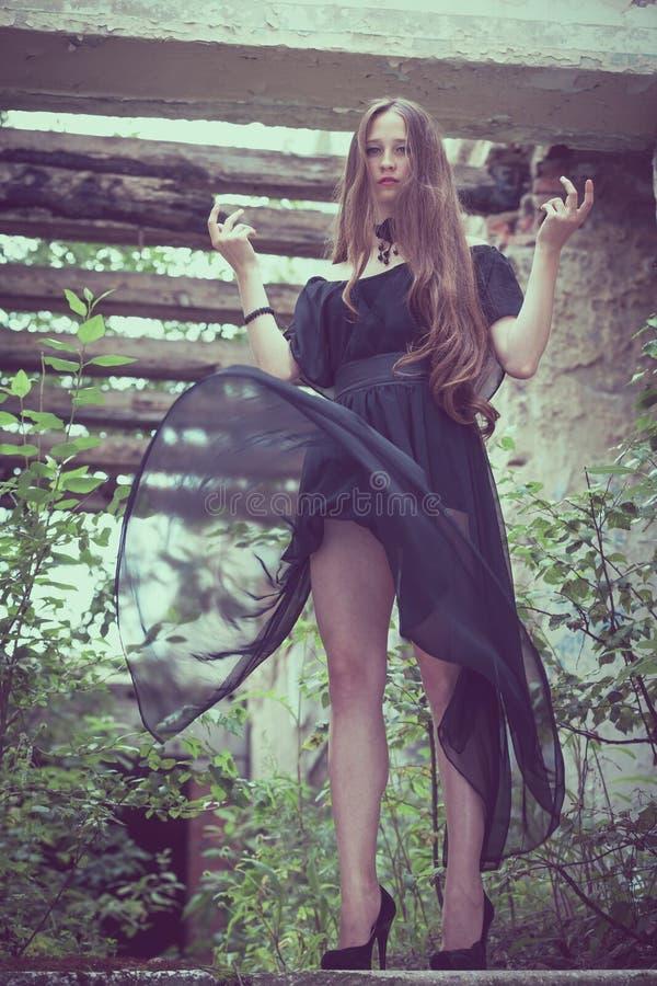 一个美丽的年轻哀伤的goth女孩的画象一被放弃的老的 免版税库存图片