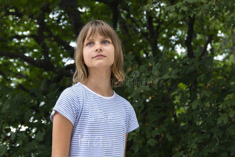 一个美丽的liitle女孩特写镜头的画象在绿色叶子背景的  免版税库存图片