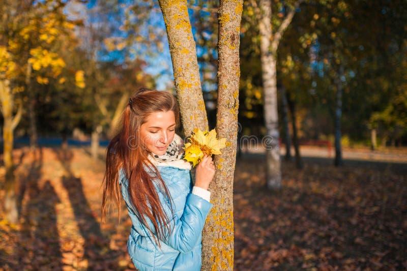 一个美丽,梦想和快乐的女孩的秋天森林画象的女孩有长的波浪发的在一件白色秋天外套 库存照片