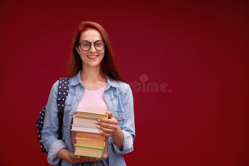 一个美女女学生和堆的画象有背包的书在他的手上对红色背景微笑着 免版税库存照片