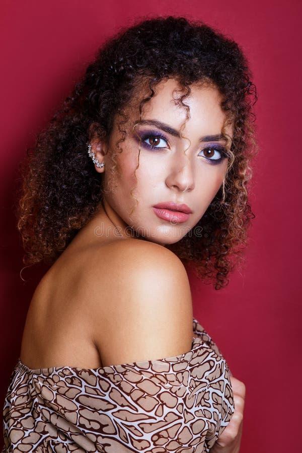 一个美好的年轻非裔美国人的女性时装模特儿的特写镜头画象与卷发的 免版税库存照片