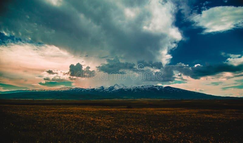 一个美好的领域的宽射击与惊人的积雪的落矶山脉的与令人惊讶的云彩 免版税库存照片