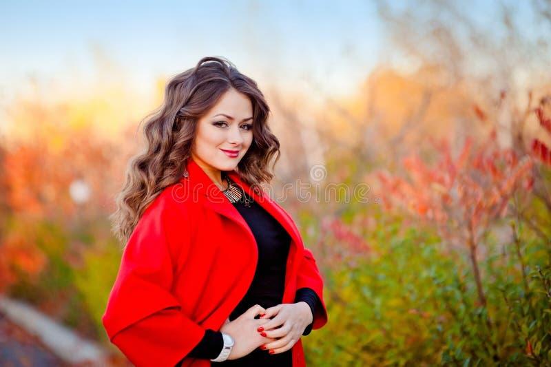 一个美妙地美丽的女孩的画象一件红色外套的 库存图片