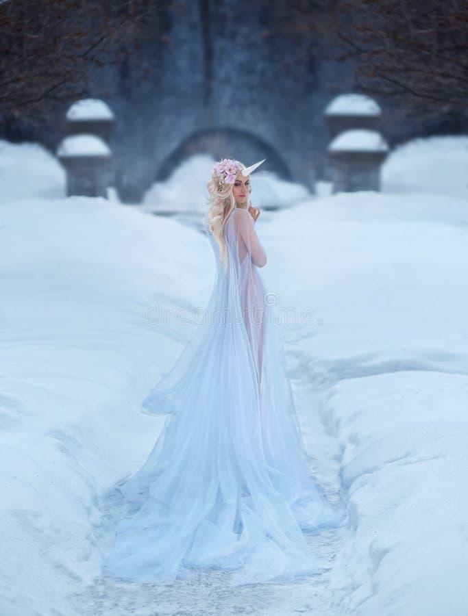 一个美妙的生物,光的,白色,有一点透明礼服一个独角兽女孩,通过雪走 的treadled 免版税库存照片