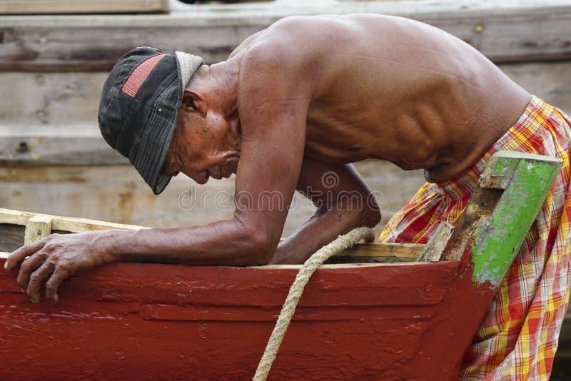 一个老人为一条残破的小船服务 免版税库存图片