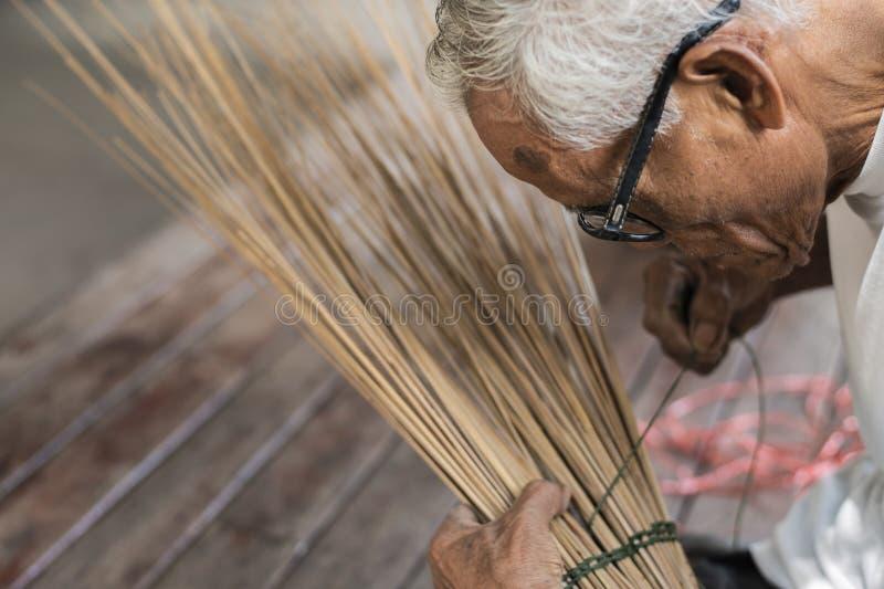 一个老人的特写镜头图象编织一条绳索做笤帚 免版税图库摄影