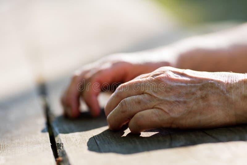 一个老人的年迈的手在桌上的 免版税库存照片