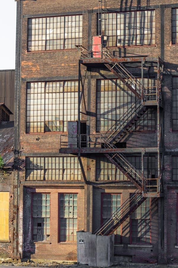 一个老仓库大厦的外部与砖,窗口,防火梯的 库存图片